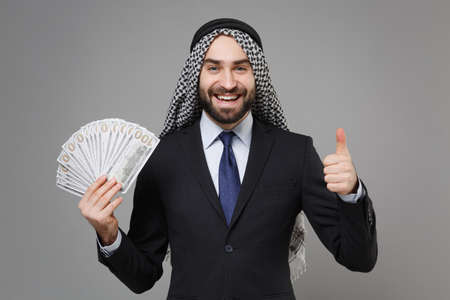 Smiling bearded arabian muslim businessman in keffiyeh kafiya ring igal agal black suit isolated on gray background. Achievement career wealth business concept Hold fan of cash money showing thumb up. Standard-Bild