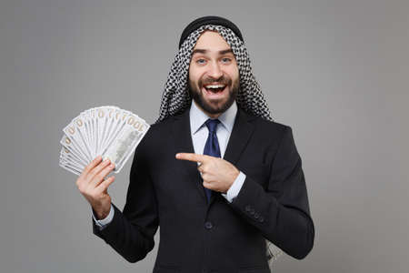 Excited bearded arabian muslim businessman in keffiyeh kafiya ring igal agal black suit isolated on gray background. Achievement career wealth business concept Point index finger on fan of cash money.