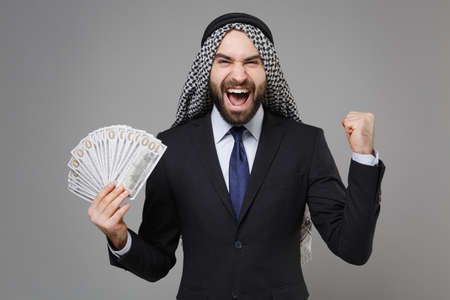 Happy young arabian muslim businessman in keffiyeh kafiya ring igal agal black suit isolated on gray background. Achievement career wealth business concept Hold fan of cash money doing winner gesture.