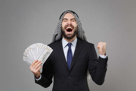 Overjoyed arabian muslim businessman in keffiyeh kafiya ring igal agal black suit isolated on gray background. Achievement career wealth business concept. Hold fan of cash money doing winner gesture. Stock Photo