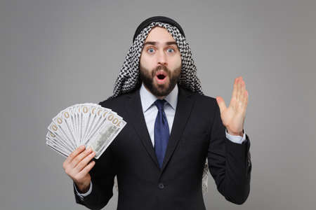Shocked bearded arabian muslim businessman in keffiyeh kafiya ring igal agal suit isolated on gray background. Achievement career wealth business concept. Hold fan of cash money in dollar banknotes. Standard-Bild