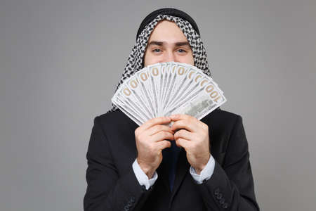 Funny arabian muslim businessman in keffiyeh kafiya ring igal agal classic black suit isolated on gray background. Achievement career wealth business concept. Covering face with fan of cash money. Standard-Bild