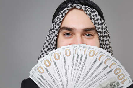 Close up of young arabian muslim businessman in keffiyeh kafiya ring igal agal isolated on gray background in studio. Achievement career wealth business concept. Covering face with fan of cash money.