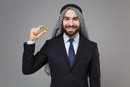 Smiling young bearded arabian muslim businessman in keffiyeh kafiya ring igal agal classic suit isolated on gray background. Achievement career wealth business concept. Hold bitcoin, future currency.