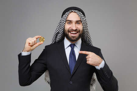 Funny arabian muslim businessman in keffiyeh kafiya ring igal agal classic suit isolated on gray background. Achievement career wealth business concept. Point index finger on bitcoin, future currency.