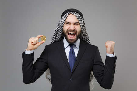 Happy arabian muslim businessman in keffiyeh kafiya ring igal agal suit isolated on gray background. Achievement career wealth business concept. Hold bitcoin, future currency, doing winner gesture.