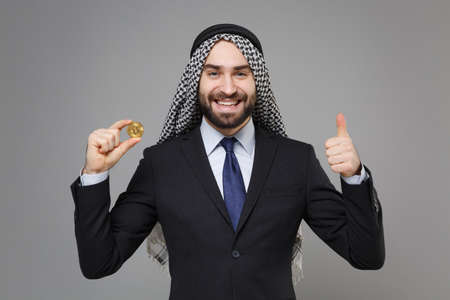 Smiling arabian muslim businessman in keffiyeh kafiya ring igal agal black suit isolated on gray background. Achievement career wealth business concept. Hold bitcoin, future currency showing thumb up.