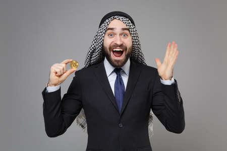 Surprised arabian muslim businessman in keffiyeh kafiya ring igal agal black suit isolated on gray background. Achievement career wealth business concept. Hold bitcoin future currency spreading hands.
