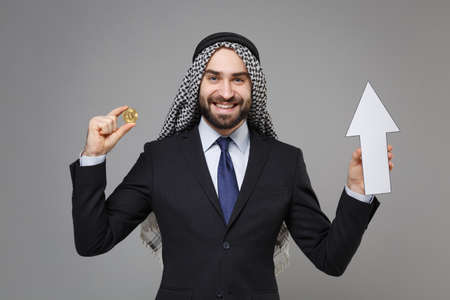 Smiling bearded arabian muslim businessman in keffiyeh kafiya ring igal agal black suit isolated on gray background. Achievement career wealth business concept. Hold bitcoin future currency, up arrow. Banco de Imagens
