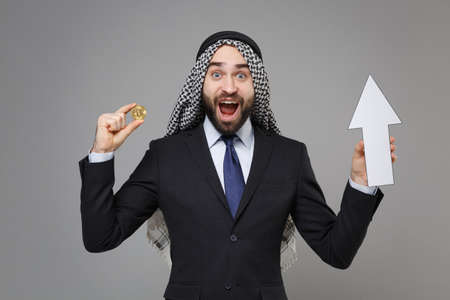 Shocked bearded arabian muslim businessman in keffiyeh kafiya ring igal agal black suit isolated on gray background. Achievement career wealth business concept. Hold bitcoin future currency, up arrow.