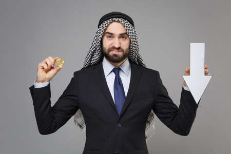 Displeased arabian muslim businessman in keffiyeh kafiya ring igal agal black suit isolated on gray background. Achievement career wealth business. Hold bitcoin future currency, down value fall arrow.
