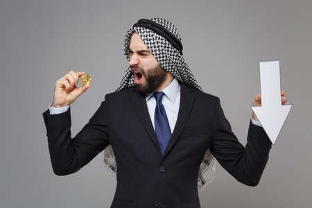 Perplexed arabian muslim businessman in keffiyeh kafiya ring igal agal black suit isolated on gray background. Achievement career wealth business. Hold bitcoin future currency, down value fall arrow. Banco de Imagens