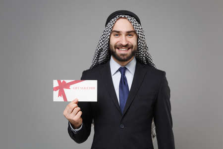 Smiling bearded arabian muslim businessman in keffiyeh kafiya ring igal agal classic black suit shirt isolated on gray background. Achievement career wealth business concept. Hold gift certificate. Banco de Imagens - 156217460