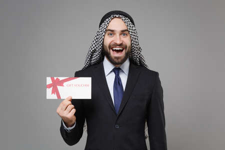 Surprised bearded arabian muslim businessman in keffiyeh kafiya ring igal agal classic black suit shirt isolated on gray background. Achievement career wealth business concept. Hold gift certificate. Banco de Imagens