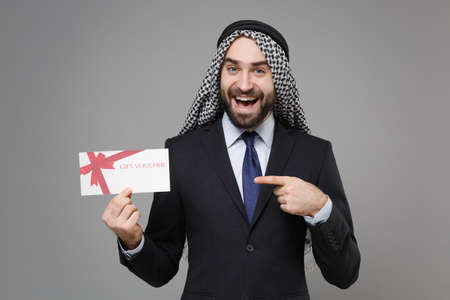 Funny bearded arabian muslim businessman in keffiyeh kafiya ring igal agal classic suit isolated on gray background. Achievement career wealth business concept. Point index finger on gift certificate.