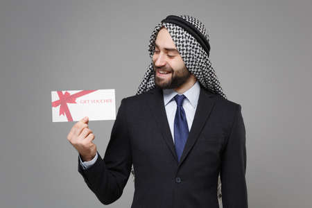 Smiling bearded arabian muslim businessman in keffiyeh kafiya ring igal agal classic black suit shirt isolated on gray background. Achievement career wealth business concept. Hold gift certificate.