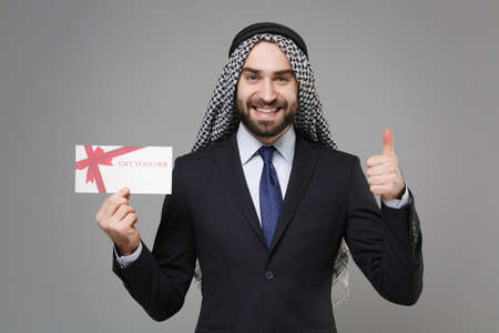 Smiling bearded arabian muslim businessman in keffiyeh kafiya ring igal agal black suit isolated on gray background. Achievement career wealth business concept. Hold gift certificate showing thumb up.