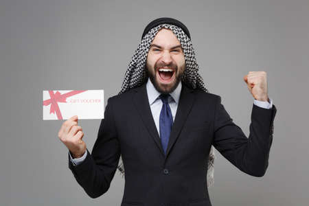 Joyful bearded arabian muslim businessman in keffiyeh kafiya ring igal agal suit isolated on gray background. Achievement career wealth business concept. Hold gift certificate doing winner gesture.