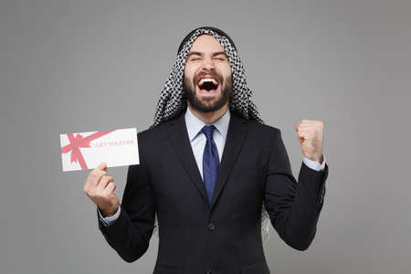 Overjoyed bearded arabian muslim businessman in keffiyeh kafiya ring igal agal suit isolated on gray background. Achievement career wealth business concept. Hold gift certificate doing winner gesture. Banco de Imagens