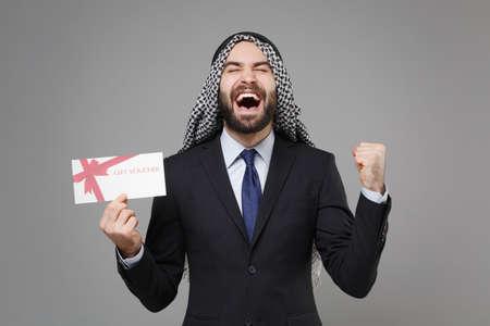 Overjoyed bearded arabian muslim businessman in keffiyeh kafiya ring igal agal suit isolated on gray background. Achievement career wealth business concept. Hold gift certificate doing winner gesture. Standard-Bild