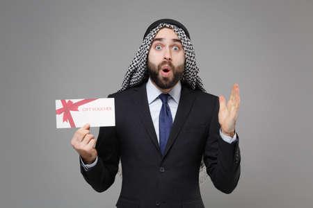 Shocked bearded arabian muslim businessman in keffiyeh kafiya ring igal agal black suit isolated on gray background. Achievement career wealth business concept. Hold gift certificate spreading hands.