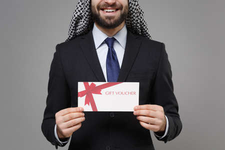 Cropped image of smiling bearded arabian muslim businessman in keffiyeh kafiya ring igal agal black suit isolated on gray background. Achievement career wealth business concept. Hold gift certificate.