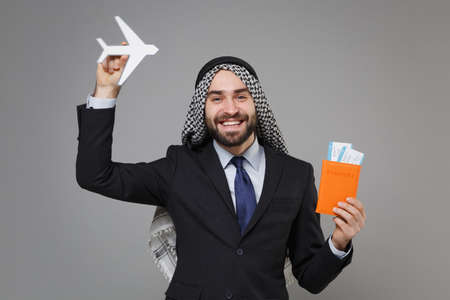 Smiling bearded arabian muslim businessman in keffiyeh kafiya ring igal agal classic black suit isolated on gray background. Achievement career wealth business concept. Hold passport ticket air plane.