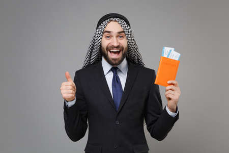 Funny arabian muslim businessman in keffiyeh kafiya ring igal agal suit isolated on gray background. Achievement career wealth business concept. Hold passport boarding pass ticket showing thumb up.