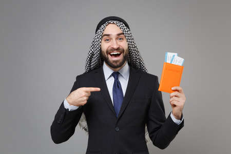 Cheerful arabian muslim businessman in keffiyeh kafiya ring igal agal suit isolated on gray background. Achievement career wealth business concept. Point index finger on passport boarding pass ticket.