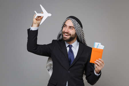 Cheerful bearded arabian muslim businessman in keffiyeh kafiya ring igal agal classic black suit isolated on gray background. Achievement career wealth business concept Hold passport ticket air plane. Banco de Imagens