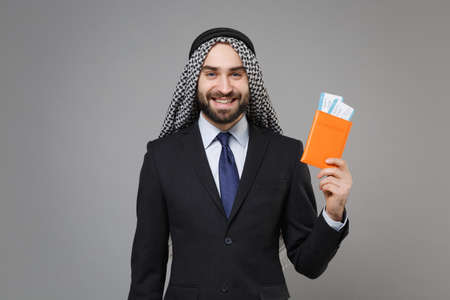 Smiling bearded arabian muslim businessman in keffiyeh kafiya ring igal agal classic suit isolated on gray background. Achievement career wealth business concept. Hold passport boarding pass ticket. Banco de Imagens
