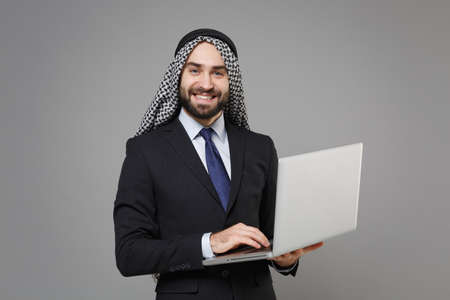 Smiling bearded arabian muslim businessman in keffiyeh kafiya ring igal agal classic black suit isolated on gray background. Achievement career wealth business concept. Working on laptop pc computer. Banco de Imagens