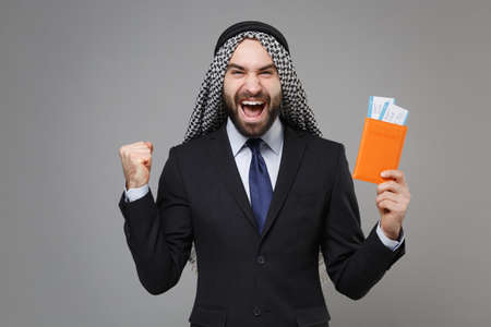 Happy arabian muslim businessman in keffiyeh kafiya ring igal agal suit isolated on gray background. Achievement career wealth business concept Hold passport boarding pass ticket doing winner gesture.