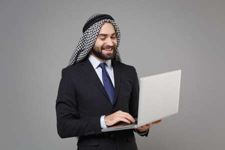 Smiling bearded arabian muslim businessman in keffiyeh kafiya ring igal agal classic black suit isolated on gray background. Achievement career wealth business concept. Working on laptop pc computer. Banco de Imagens - 156217513