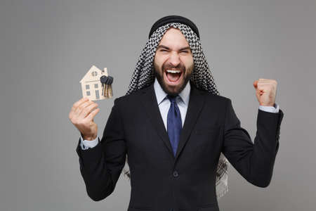 Joyful arabian muslim businessman in keffiyeh kafiya ring igal agal black suit isolated on gray background. Achievement career wealth business concept. Hold house, bunch of keys doing winner gesture. Banque d'images