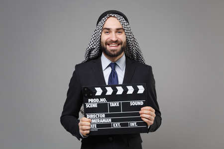 Smiling bearded arabian muslim businessman in keffiyeh kafiya ring igal agal suit isolated on gray background. Achievement career wealth business concept. Hold classic black film making clapperboard. Stock Photo