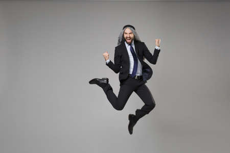 Joyful bearded arabian muslim businessman in keffiyeh kafiya ring igal agal classic suit isolated on gray background. Achievement career wealth business concept. Jumping, clenching fists like winner.