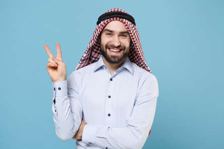 Smiling bearded arabian muslim man in keffiyeh kafiya ring igal agal casual clothes isolated on pastel blue background. People religious lifestyle concept. Mock up copy space. Showing victory sign.