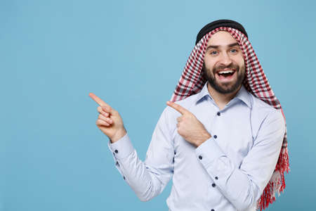 Cheerful young bearded arabian muslim man in keffiyeh kafiya ring igal agal casual clothes isolated on pastel blue wall background. People religious lifestyle concept. Pointing index fingers up aside.
