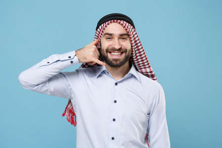 Smiling bearded arabian muslim man in keffiyeh kafiya ring igal agal casual clothes isolated on pastel blue background. People religious lifestyle concept. Doing phone gesture like says call me back.