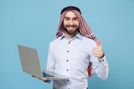 Smiling bearded arabian muslim man in keffiyeh kafiya ring igal agal casual clothes isolated on pastel blue background. People religious lifestyle concept. Work on laptop pc computer showing thumb up.