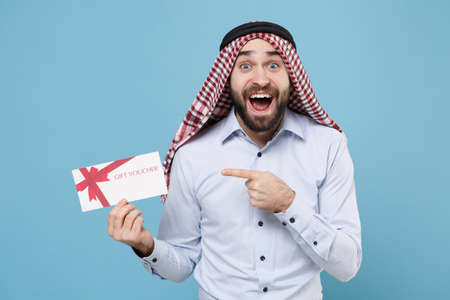 Excited bearded arabian muslim man in keffiyeh kafiya ring igal agal casual clothes isolated on pastel blue background.
