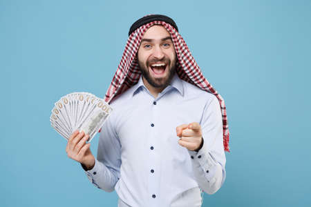 Excited arabian muslim man in keffiyeh kafiya ring igal agal casual clothes isolated on pastel blue background. Stock Photo