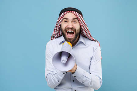 Cheerful bearded arabian muslim man in keffiyeh kafiya ring igal agal casual clothes isolated on pastel blue background.