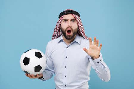 Bewildered arabian muslim man in keffiyeh kafiya ring igal agal casual clothes isolated on pastel blue background. 免版税图像