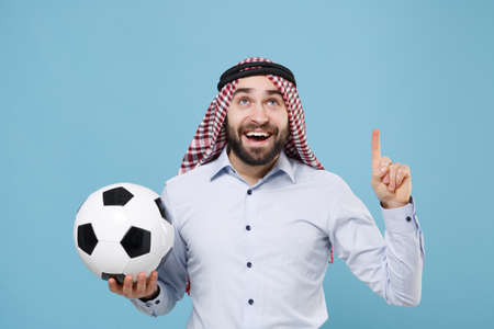 Funny arabian muslim man in keffiyeh kafiya ring igal agal casual clothes isolated on blue background. Stock Photo