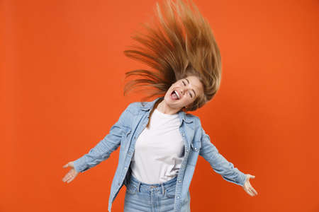 Excited young woman girl in casual denim clothes posing isolated on orange background in studio.