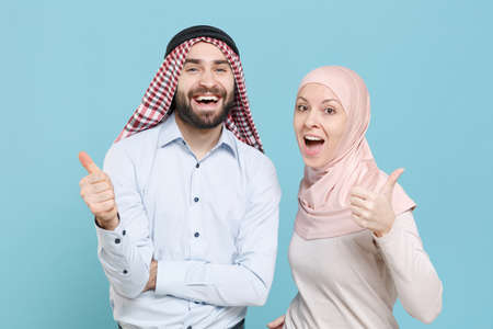Cheerful young couple friends arabian muslim man wonam in keffiyeh kafiya ring igal agal hijab clothes isolated on blue background in studio.
