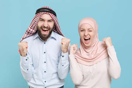 Joyful young couple friends arabian muslim man woman in keffiyeh kafiya ring igal agal hijab clothes isolated on blue background in studio.