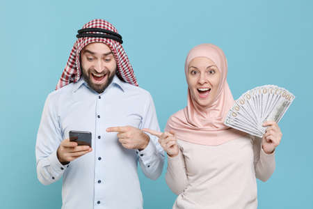 Amazed couple friends arabian muslim man wonam in keffiyeh kafiya ring agal hijab clothes isolated on blue background.